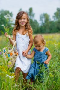 Two adorable girl walking on the meadow